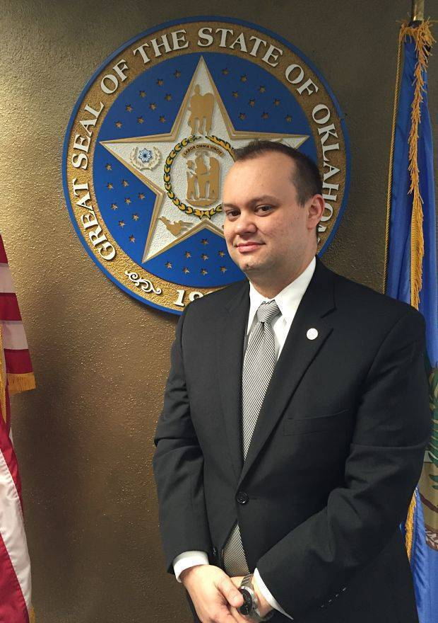William R. Pierce, criminal defense lawyer OKC standing next to the Great Seal of the State of Oklahoma.